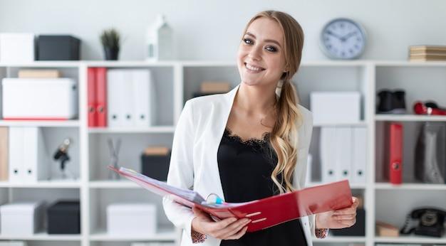 Una niña se encuentra en la oficina al lado del estante y sostiene una carpeta con documentos en sus manos.