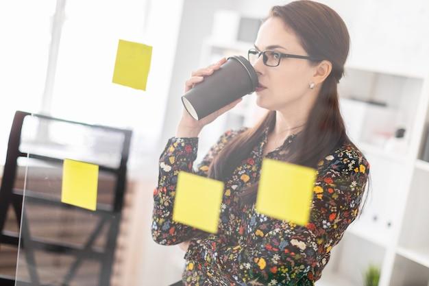 Una niña se encuentra en la oficina cerca de un tablero transparente con pegatinas y bebe café.