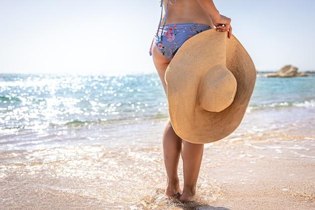 Una niña se encuentra en la orilla del mar de arena con un sombrero en la mano.