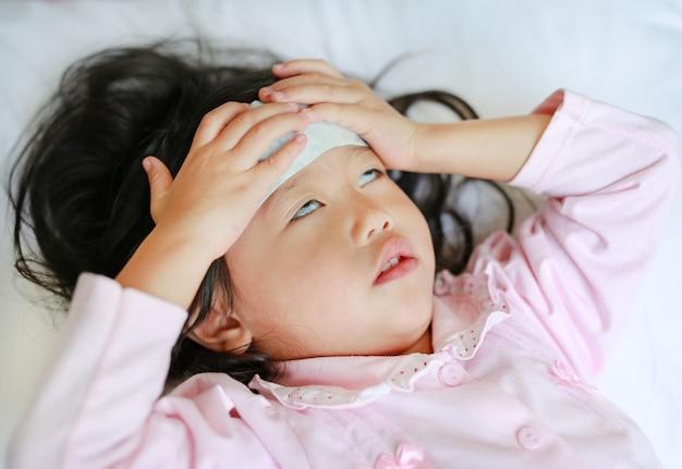 Niña enferma acostada en la cama con una gelatina fría en la cara