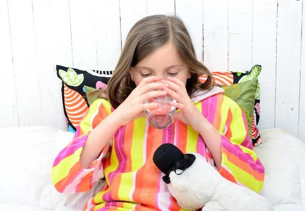 Una niña enferma bebiendo un vaso de agua