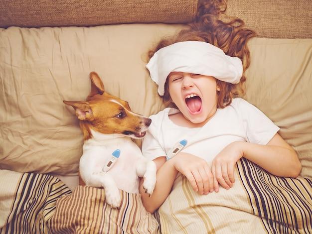 Niña enferma y cachorro debajo de la colcha