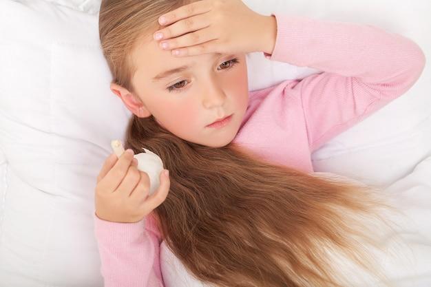 Niña enferma en la cama estornudando en pañuelo en el dormitorio