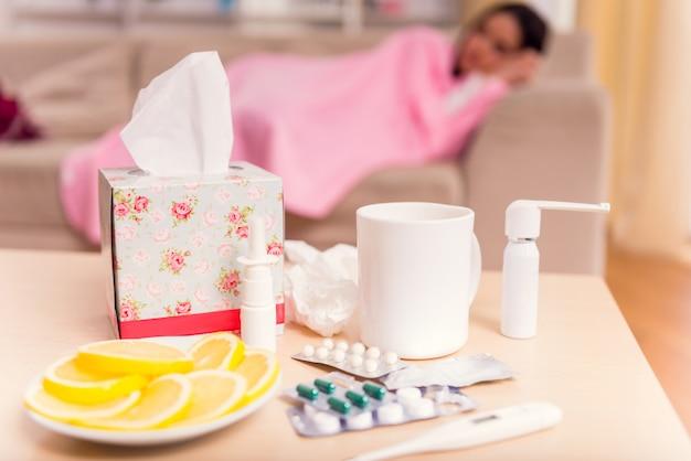 Niña enferma durmiendo en casa en el primer plano de la medicación.