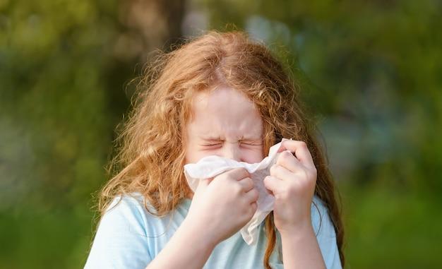 Niña enferma estornuda en un pañuelo al aire libre.