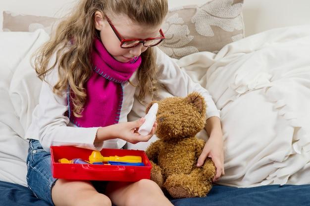 Niña enferma con gafas cura a su osito de peluche enfermo