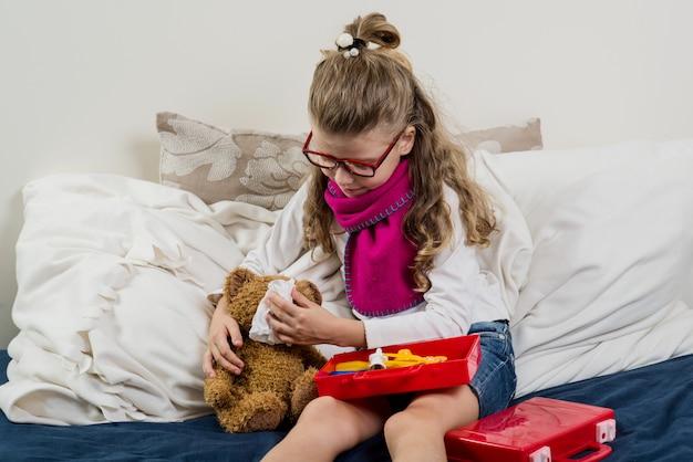Niña enferma con gafas, cura a su osito de peluche enfermo