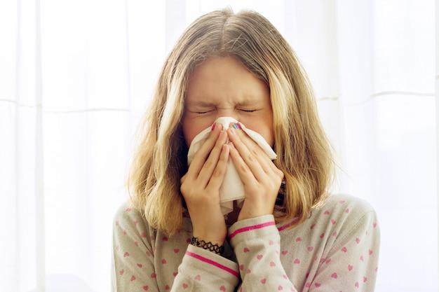 Niña enferma con pañuelo en la casa.