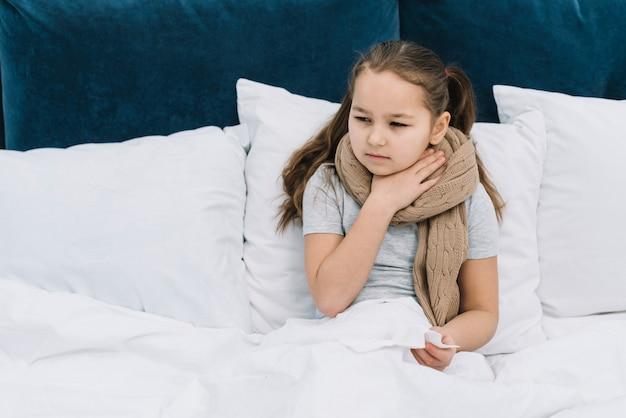 Niña enferma sentada en la cama con una bufanda alrededor del cuello sufriendo dolor de cuello