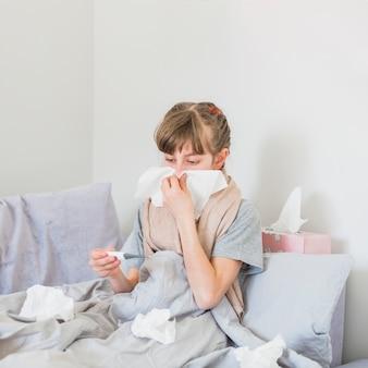 Niña enferma sonándose la nariz