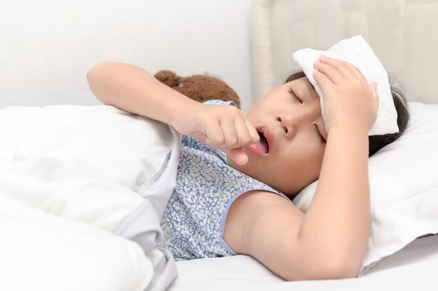 Niña enferma está tosiendo y dolor de garganta acostado en la cama