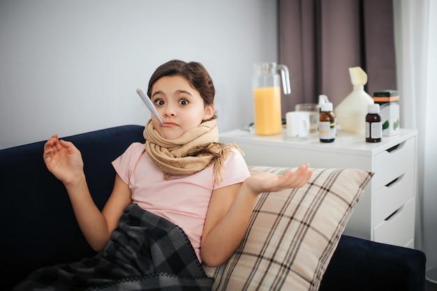 Niña enferma tumbado en el sofá. ella mira a la cámara. chica sostenga el termómetro en la boca. el niño se ve asombrado. ella está sola en la habitación.
