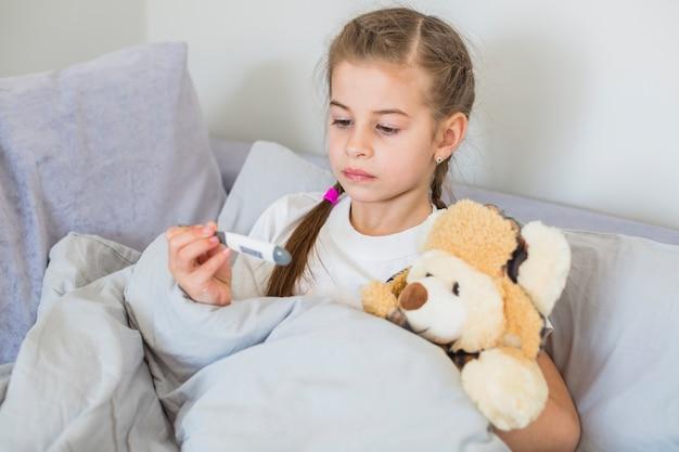 Niña enferma usando el termómetro