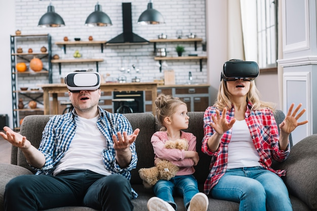Niña enojada mirando a sus padres mientras madre con gafas de realidad virtual en casa