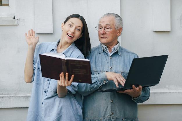 Niña enseñando a su abuelo a usar una computadora portátil