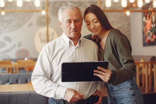 Niña enseñando a su abuelo a usar una tableta