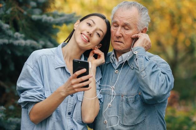 Niña enseñando a su abuelo a usar un teléfono