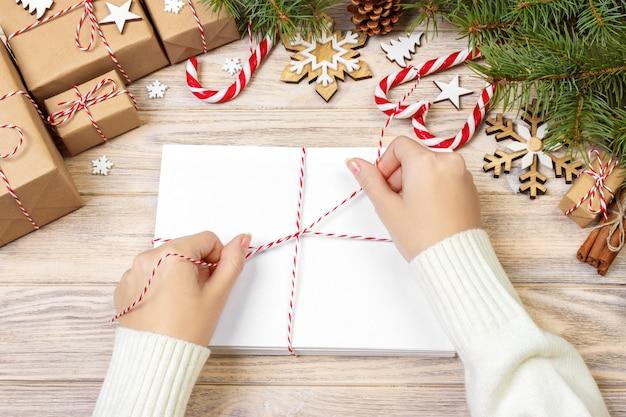 Niña envuelve cartas de navidad en sobres, niños carta de santa claus en sobres, fondo de navidad