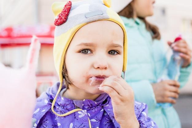 La niña es dulce, algodón de azúcar, alegría, caminar con la familia.
