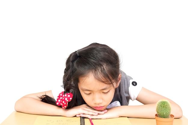 Una niña es infeliz haciendo la tarea.
