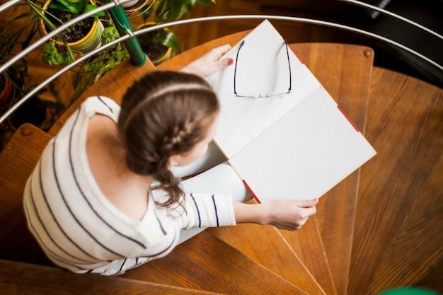 La niña en la escalera leyendo un libro.