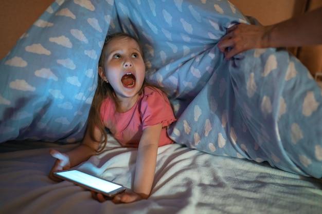 Niña escondida debajo de la manta con el teléfono inteligente en la noche cuando todos están dormidos