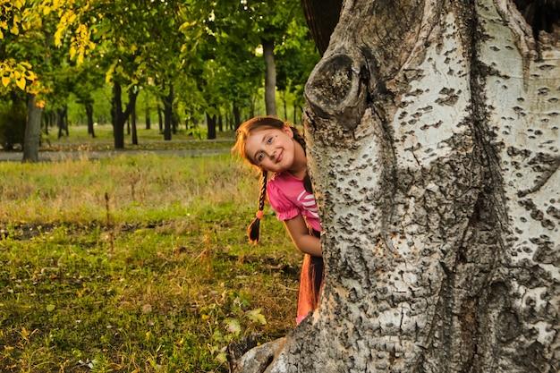 Niña escondida detrás de un árbol.