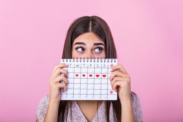 Niña escondida detrás de un calendario menstrual y mirando a otro lado
