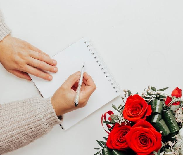 La niña escribe en la vista superior de un cuaderno