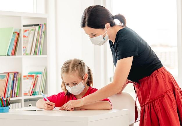 Niña escribiendo en un cuaderno con la ayuda del maestro en la escuela durante la epidemia del virus