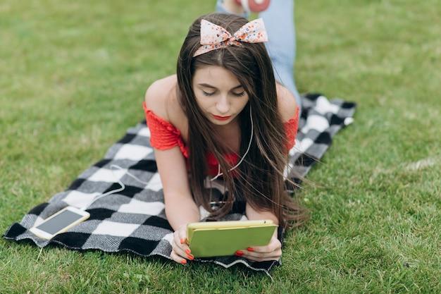 La niña escucha música en los auriculares con su teléfono inteligente, usa un gadget