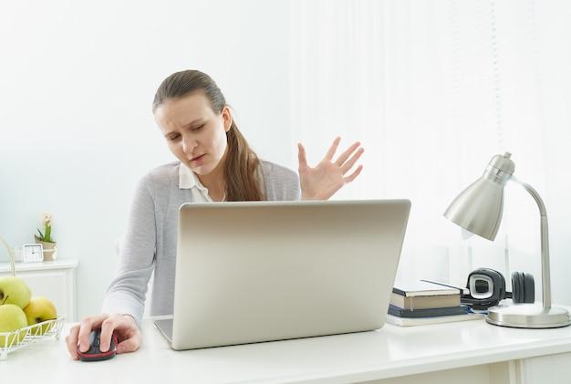 La niña escucha o mira la información en la computadora con incredulidad. expresión escéptica.
