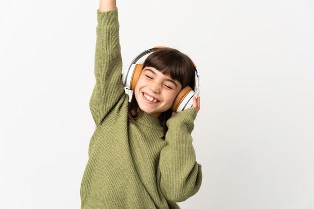 Niña escuchando música con un móvil aislado en la pared blanca escuchando música y bailando