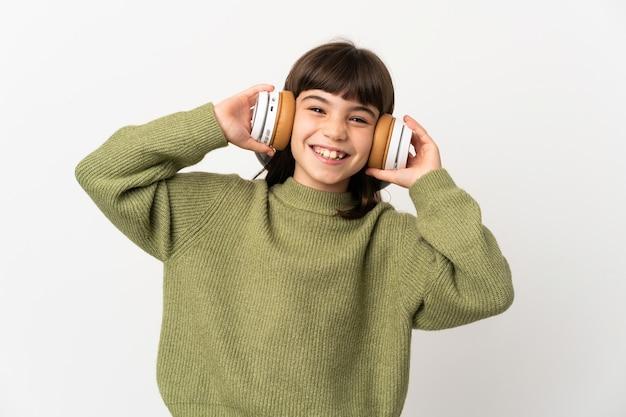 Niña escuchando música con un móvil aislado en la pared blanca escuchando música
