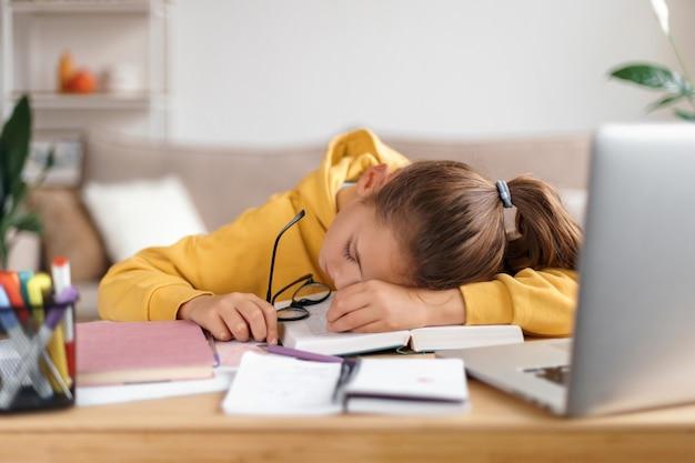 Niña de la escuela agotada durmiendo en el escritorio mientras hace muchos deberes