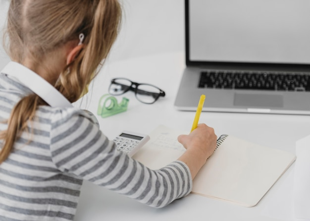 Niña de la escuela asistiendo a clases en línea
