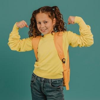 Niña de la escuela con camisa amarilla mostrando los músculos