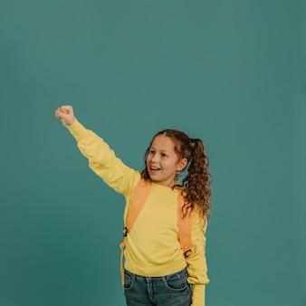 Niña de la escuela con camisa amarilla sosteniendo una mano en el aire