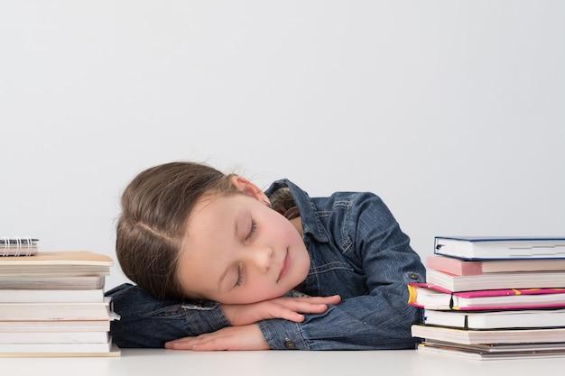 Niña de la escuela cansada durmiendo en su escritorio durante la lección