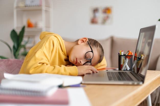 Niña de la escuela cansada en gafas durmiendo en el escritorio frente a la computadora portátil en casa, se cansó de estudiar