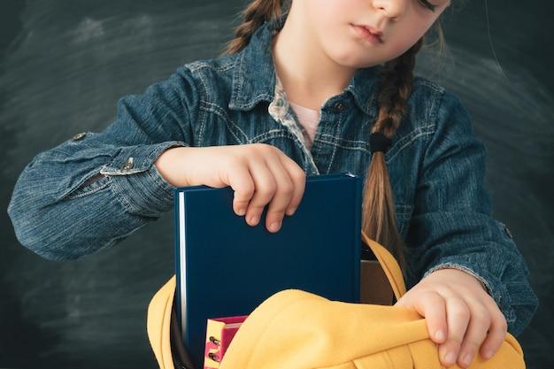 Niña de la escuela con coletas llevando espalda amarilla con libros