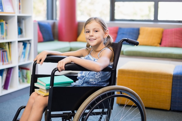 Niña de la escuela con discapacidad con libros en la biblioteca