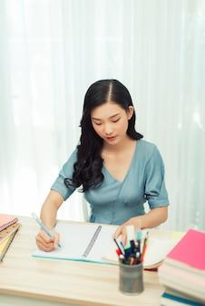Niña de la escuela enfocada estudiando con libros preparándose para el examen de prueba escribiendo un ensayo haciendo la tarea en casa
