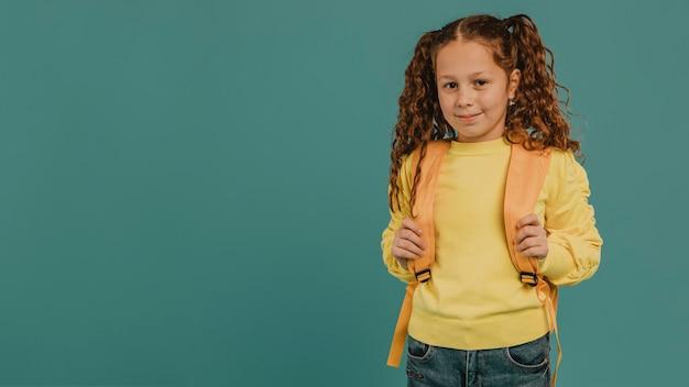 Niña de la escuela con espacio de copia de camisa amarilla