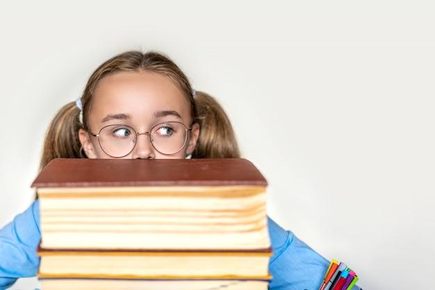 Niña de la escuela estresada, cansada de aprender con dificultad con los libros en los exámenes, preparación de exámenes, niña de la escuela secundaria abrumada y agotada, con estudios difíciles o demasiada tarea