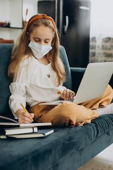 Niña de la escuela estudiando en casa con máscara, aprendizaje a distancia