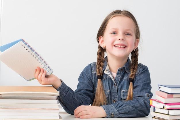 Niña de la escuela feliz sentado en el escritorio con libros.