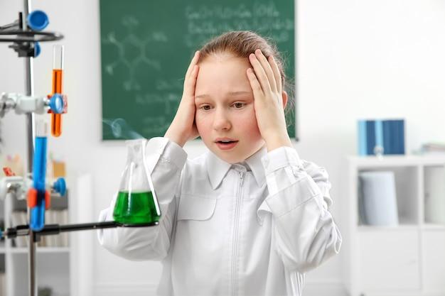 Niña de la escuela hermosa emocionada mirando el matraz en la clase de química