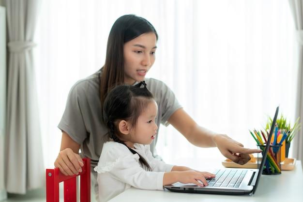 Niña de la escuela de jardín de infantes con la madre videoconferencia e-learning con el maestro en la computadora portátil