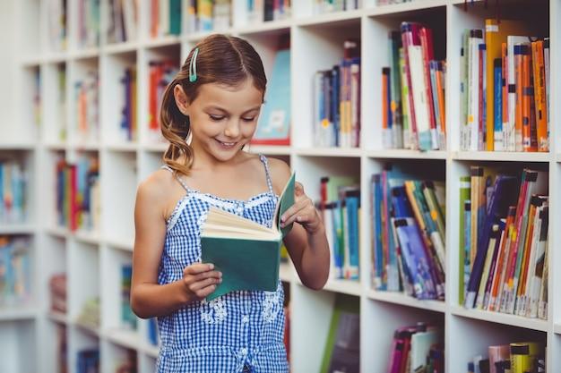 Niña de la escuela leyendo un libro en la biblioteca
